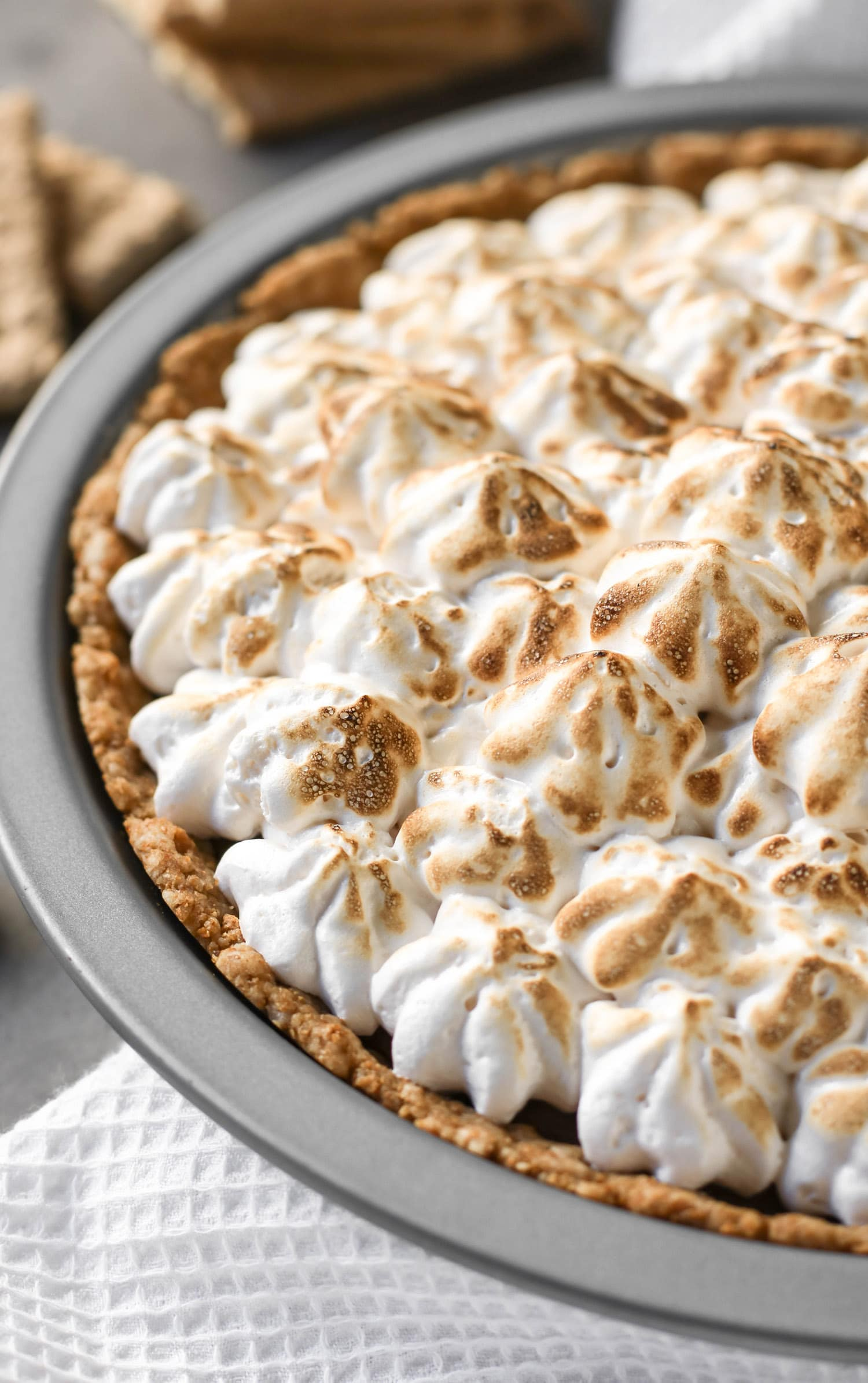 This decadent S'mores Pie has a deliciously comforting graham cracker crust, a rich and creamy chocolate filling, and a homemade marshmallow fluff topping. And it's dairy free and low in sugar! Healthy Dessert Recipes at the Desserts With Benefits Blog